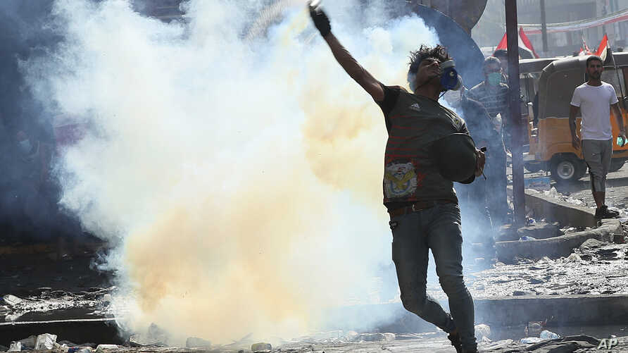 An anti-government protester prepares to throw back a tear gas canister fired by police during clashes in downtown Baghdad,…