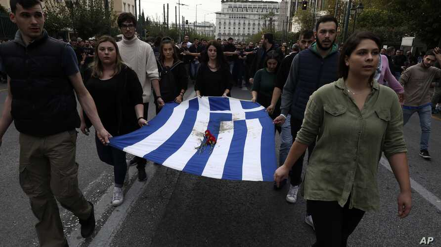 University students hold a blood-stained Greek flag from the deadly 1973 student uprising during a rally in Athens, Nov. 17, 2019.