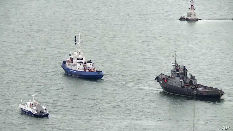 This video grab provided by the Krym 24 tv station via AP Television shows a seized Ukrainian ship, right, is towed by a Russian coast guard boat out of the port in Kerch, Crimea, Nov. 17, 2019.