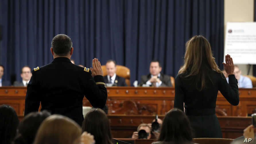 Jennifer Williams, an aide to Vice President Mike Pence, and National Security Council aide Lt. Col. Alexander Vindman, left, are sworn in to testify before the House Intelligence Committee on Capitol Hill in Washington, Tuesday, Nov. 19