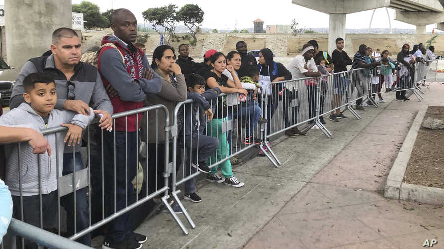 FILE - In this Thursday, Sept. 26, 2019 file photo asylum seekers in Tijuana, Mexico, listen to names being called from a…