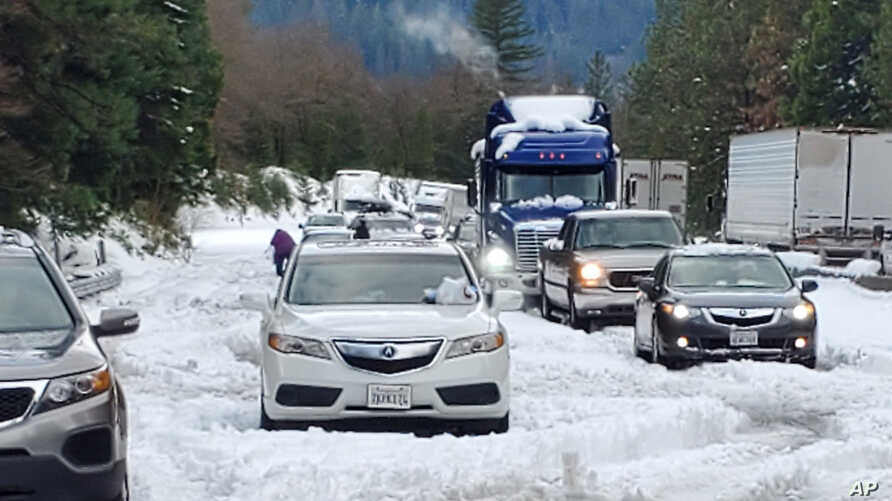 In this photo provided by Caltrans, are cars and trucks in stopped traffic on Interstate 5 near Dunsmuir, Calif., Wednesday,…