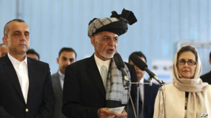 Afghan President Ashraf Ghani, center, speaks to journalists after voting at Amani high school, near the presidential palace in…