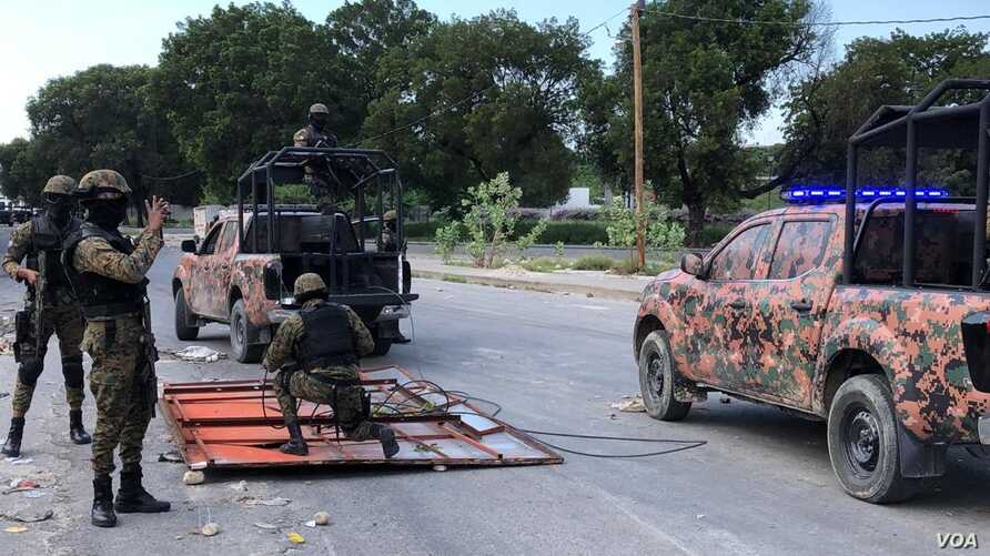 Haiti's National Police guard remove makeshift barricades made of steel fences and tree branches protesters placed to block the National Palace entrance, Oct. 31, 2019. (Photo: Matiado Vilme / VOA)