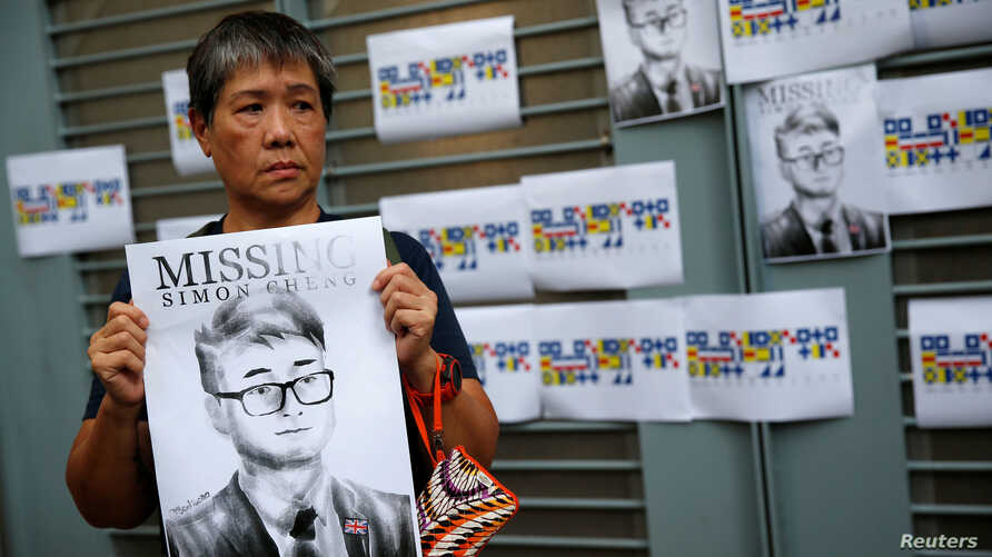A woman holds a poster of Simon Cheng, a staff member at the consulate who went missing on August 9 after visiting the neighboring mainland city of Shenzhen, during a protest outside the British Consulate-general office in Hong Kong, China, Aug. 21, 2019.