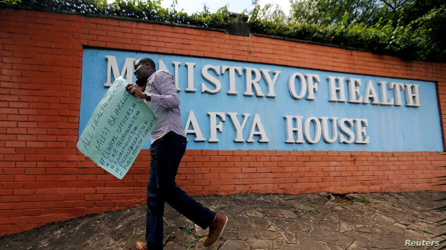 A Kenyan talks on his mobile phone outside the Ministry of Health headquarters during a strike following the failed…