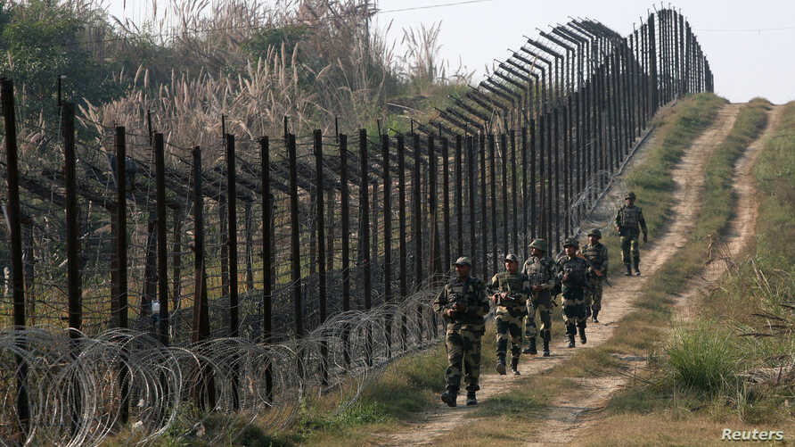Indian Border Security Force (BSF) soldiers patrol the fenced border with Pakistan at Babiya village in Hira Nagar sector,…