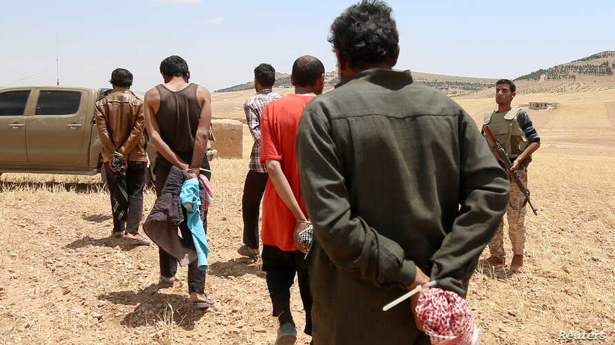 FILE PHOTO: Men, who the Democratic Forces of Syria fighters claimed were Islamic State fighters, walk as they are taken…