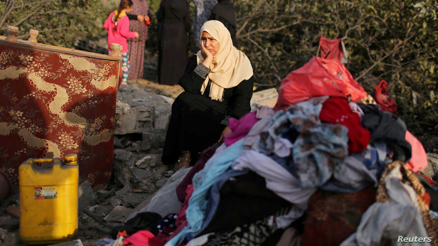 A Palestinian woman reacts as she sits at the remains of a house destroyed in an Israeli air strike in the southern Gaza Strip, Nov. 13, 2019.