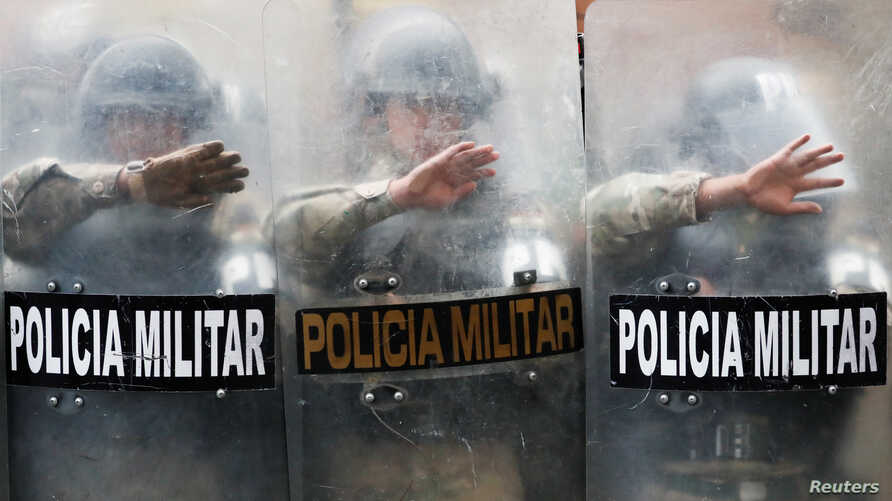 Military Police officers stand guard as supporters of former Bolivian President Evo Morales take part in a protest in La Paz,…