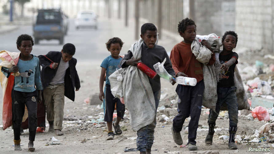 Children walk as they collect empty plastic bottles in a street in Sanaa, Yemen November 21, 2019. REUTERS/Mohamed al-Sayaghi -…