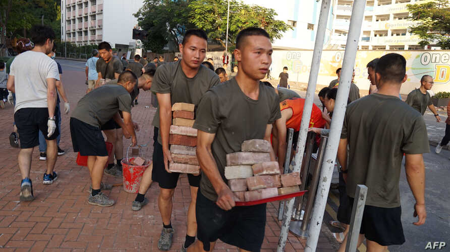 Personnel from the Chinese People's Liberation Army barracks in Hong Kong are seen on city streets Nov. 16, 2019, joining clean-up efforts after a week of violent protests. (AFP Photo/HKFP)