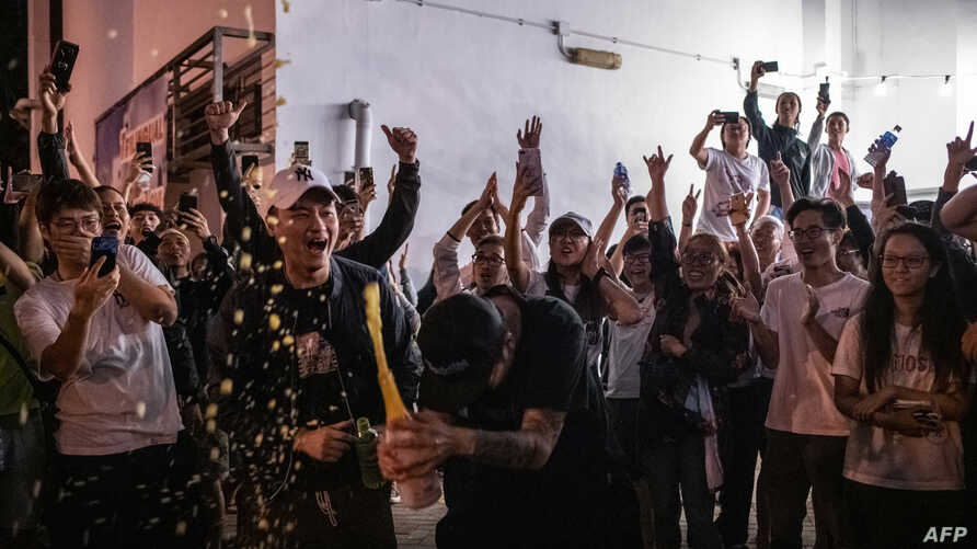 A pro-democracy supporter (C) opens a bottle of champagne outside a polling station to celebrate after a pro-Beijing lost a seat in district council elections, in Hong Kong, early Nov. 25, 2019.