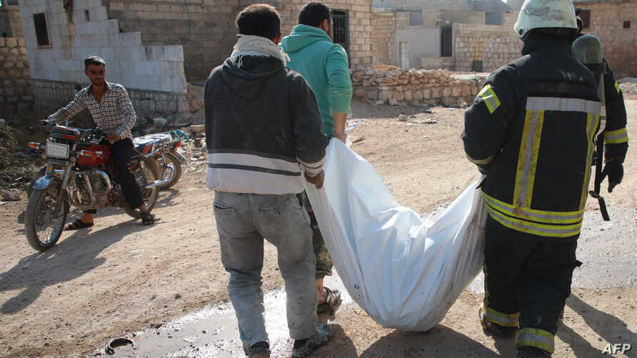 Members of the Syrian Civil Defense, also known as the White Helmets, walk with a body bag of a victim of a reported airstrike in the Syrian village of al-Sahharah in the countryside west of the northern city of Aleppo, Nov. 6, 2019.