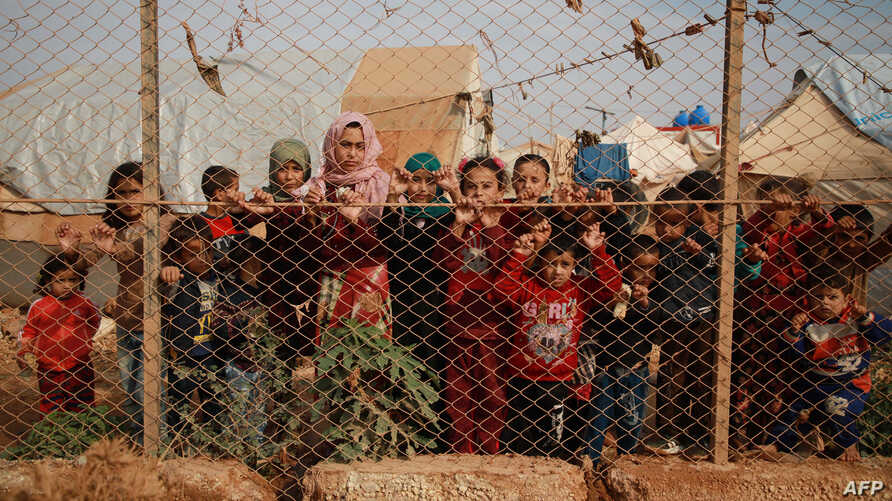Displaced Syrian children stand behind a fence outside their tents in a camp set up near the village of Kafr Lusin, in Idlib's northern countryside, near the Syria-Turkey border, Oct. 22, 2019.