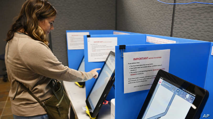 Courtney Parker votes on a new voting machine, Nov. 5, 2019, in Dallas, Georgia.