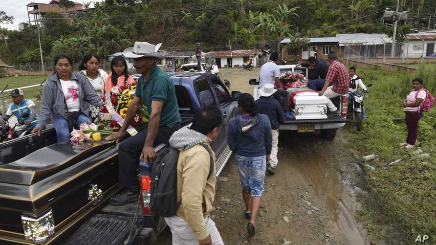 FILE - People transport the coffins of two indigenous people killed in Tacueyo, southwest Colombia, Oct. 31, 2019.