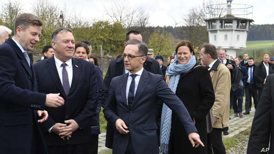 German Foreign Minister Heiko Maas, right, talks with U.S. Secretary of State Mike Pompeo, 2nd left, during their visit at the German village of Moedlareuth near Hof, eastern Germany, Nov. 7, 2019.