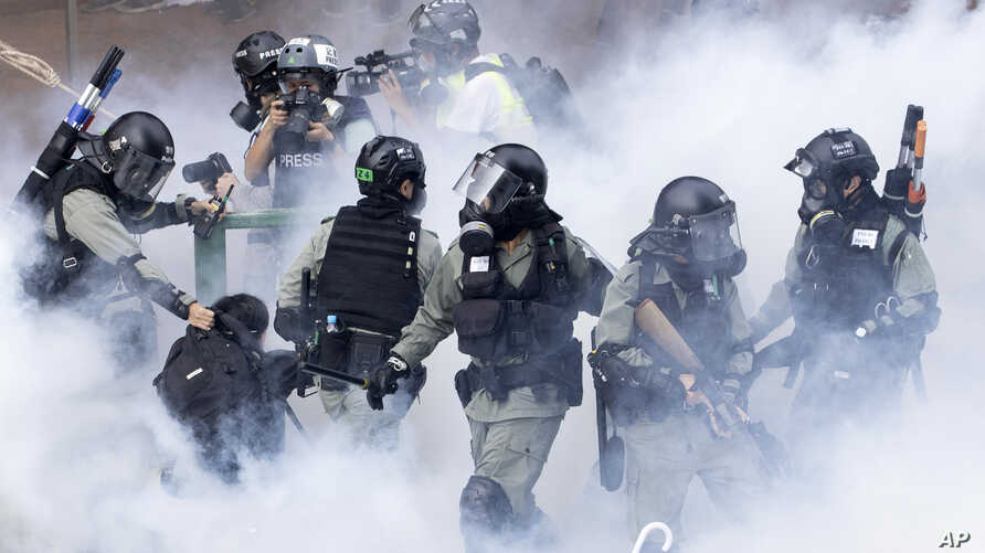 Police in riot gear move through a cloud of smoke as they detain a protester at the Hong Kong Polytechnic University.
