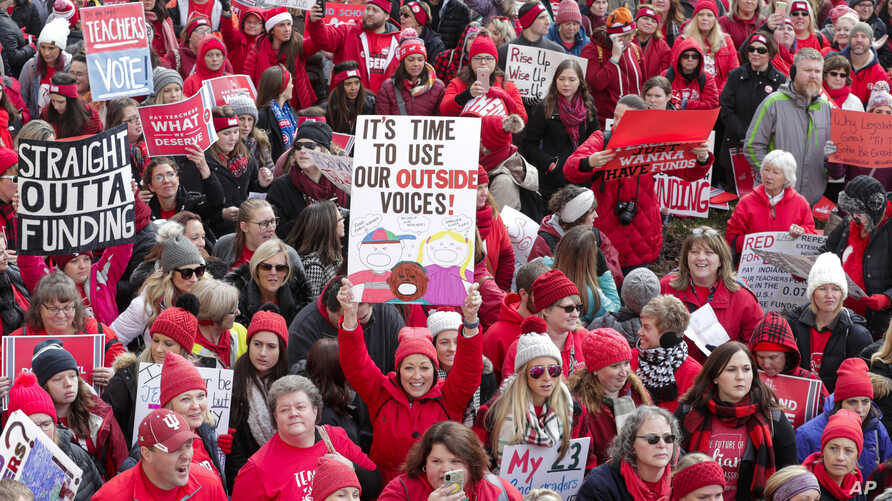 Thousands of teachers wearing red surround the Statehouse in Indianapolis, Indiana, Nov. 19, 201a9 for a rally calling for further increasing teacher pay.