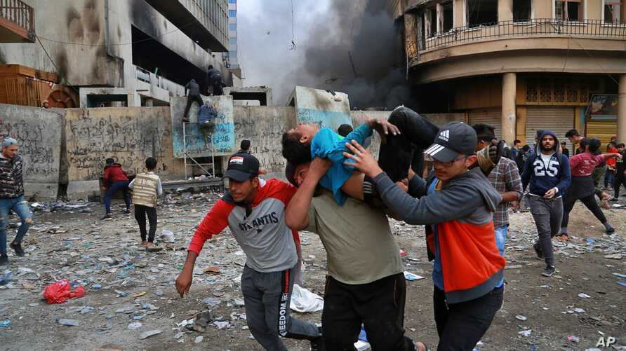 A wounded protester is carried to receive first aid during clashes with security forces on Rasheed Street in Baghdad, Iraq, Nov. 28, 2019.