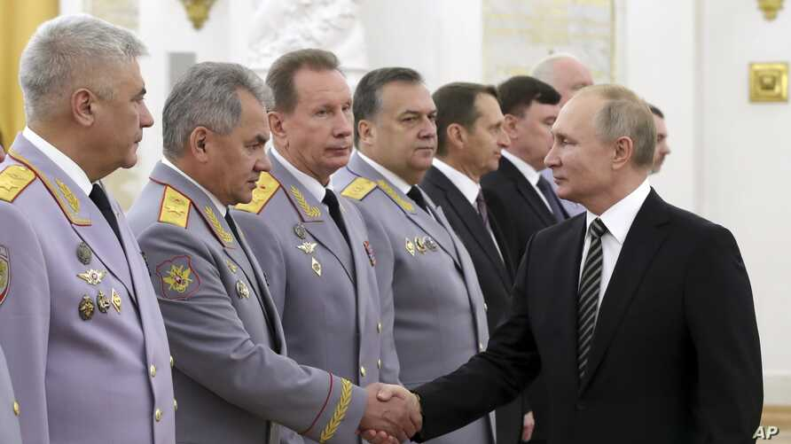 Russian President Vladimir Putin shakes hands with Defense Minister Sergei Shoigu, second left, as he greets senior military officers during a meeting in Moscow, Nov. 6, 2019.