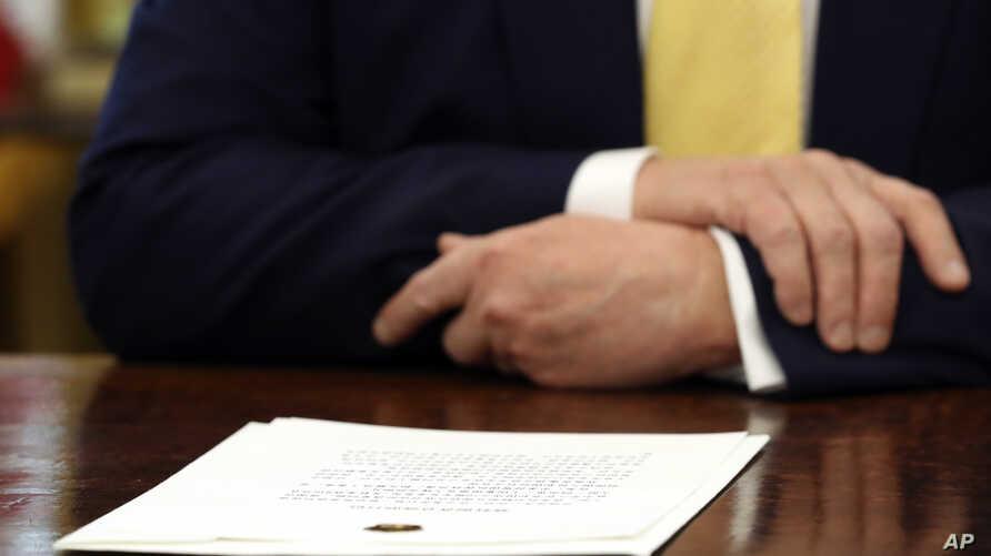 FILE - A document sits in front of President Donald Trump on his desk in the Oval Office of the White House in Washington, Oct. 11, 2019.