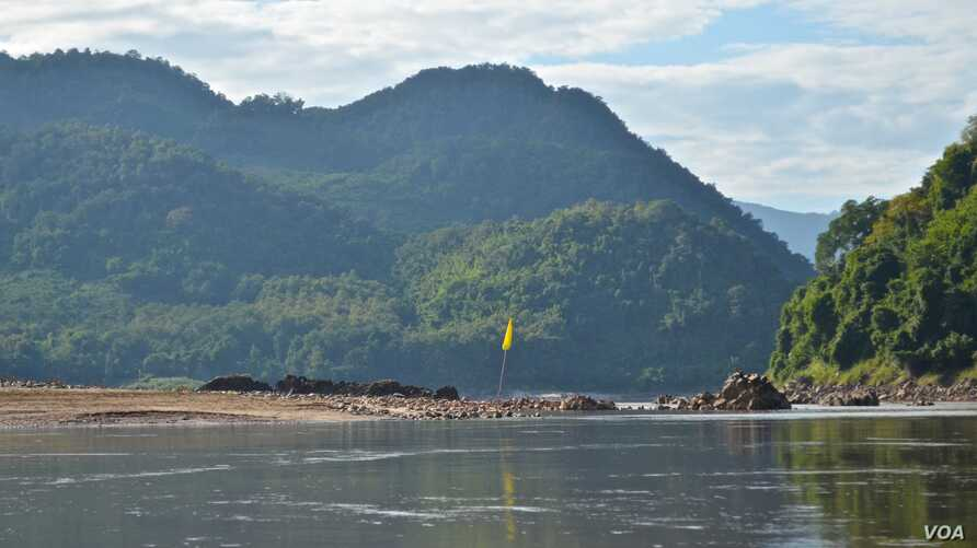 A yellow flag along the Mekong River marks the spot chosen for construction of the Luang Prabang dam near Houaygno village, Laos, Nov. 4, 2019.