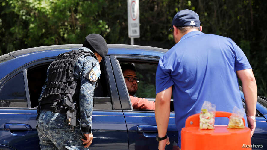 FILE -- An agent of the U.S. Department of Homeland Security and an officer of the Guatemalan border police (DIPAFRONT) question a passenger at a checkpoint in El Progreso, Guatemala, Oct. 17, 2019.