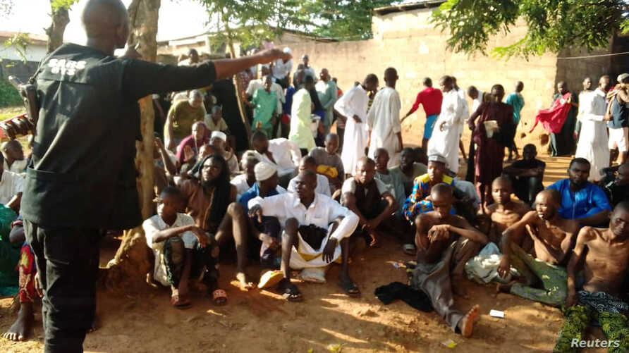 A police officer talks to people sitting on the ground after being freed by police from an Islamic rehabilitation center, in Ibadan, Nigeria, in this picture released by Nigeria Police, Nov. 5, 2019.