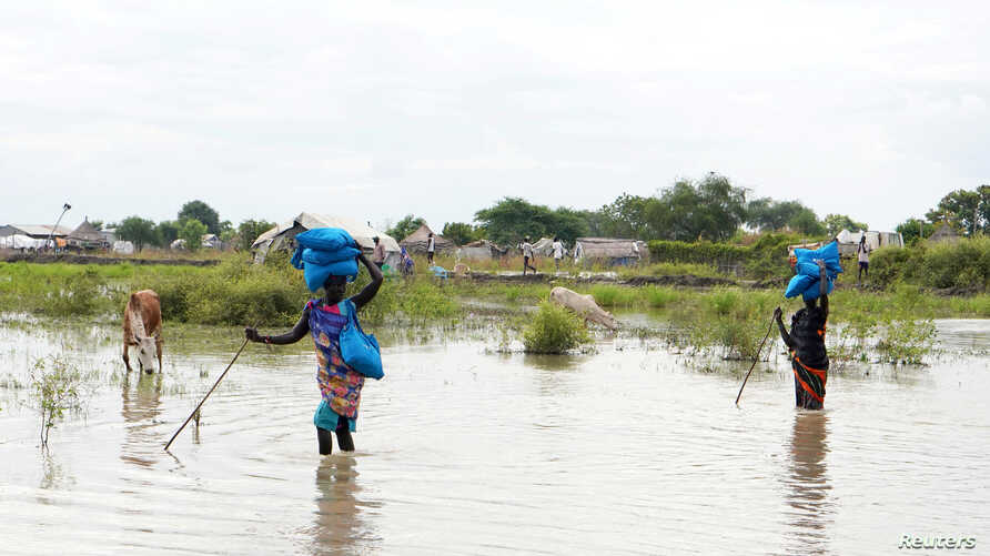 Women carry belongings on their heads as they wade through water, after heavy rains and floods forced hundreds of thousands of people to leave their homes, in the town of Pibor, Boma state, South Sudan, Nov. 6, 2019.