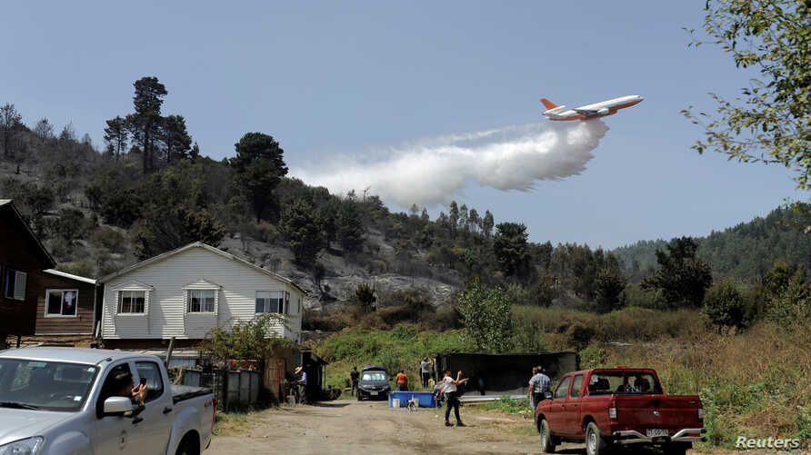 FILE - A DC-10 Air Tanker firefighting plane drops water to prevent a wildfire from spreading to homes near Concepcion, Chile, Feb. 12, 2019.