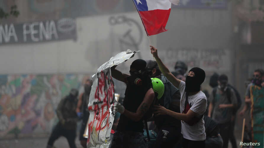 Demonstrators wave a Chile flag during a protest against Chile's government in Santiago, Chile, Nov. 11, 2019.
