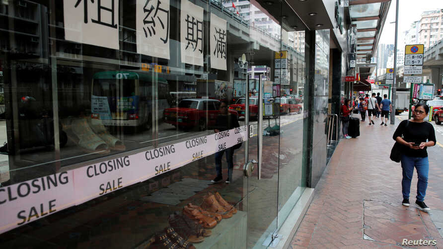 A woman walks past a shop with a closing sale in Hong Kong, China, Oct. 29, 2019.