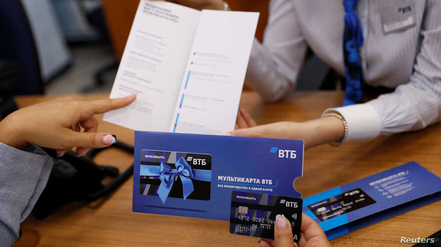 Employees demonstrate a payment card during a tour at a branch of VTB bank in Moscow, Russia, May 30, 2019.