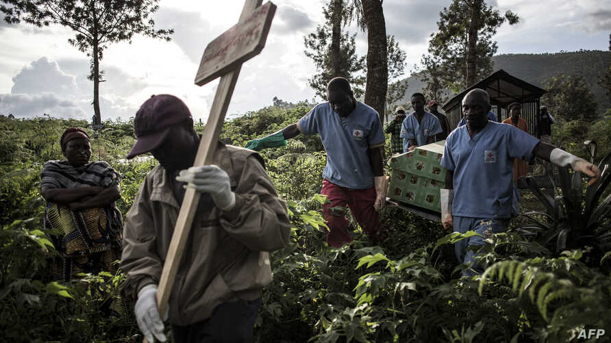 - AFP PICTURES OF THE YEAR 2019 - Health workers carry a coffin containing a victim of Ebola virus on May 16, 2019 in Butembo…