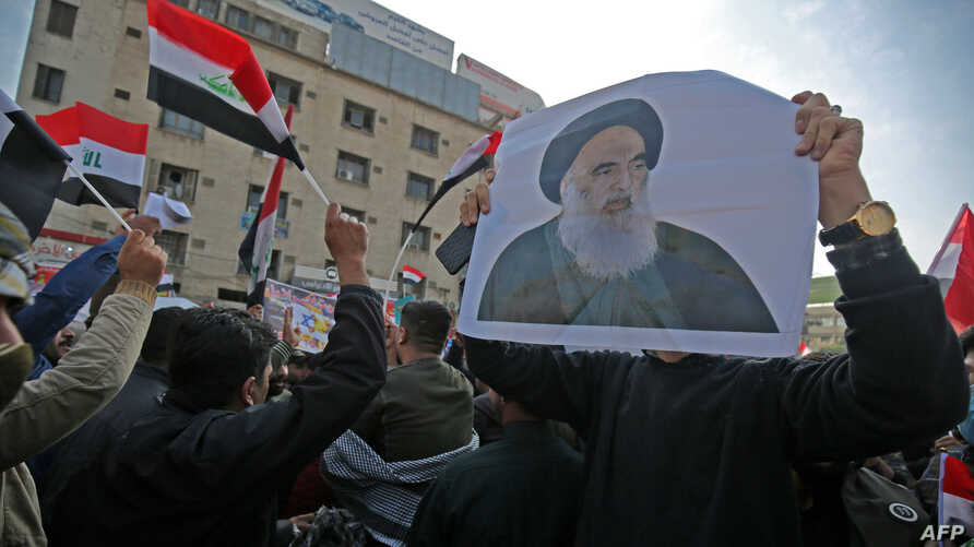 Iraqi supporters of the Hashed Al-shaabi armed network, carry  a pictures of the country's top Shiite cleric, Grand Ayatollah…