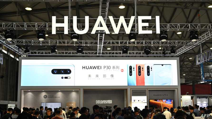 (FILES) This file photo taken on June 11, 2019 shows people gathering at a Huawei stand during the Consumer Electronics Show,…