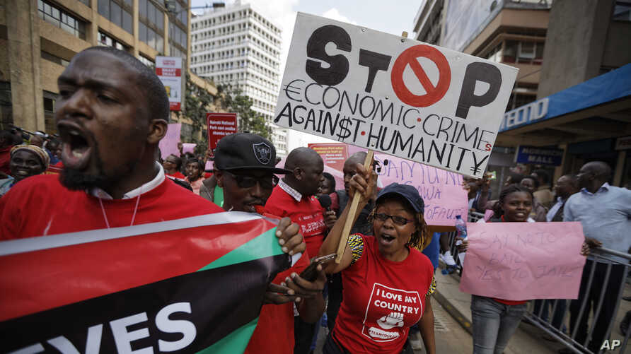 Kenyans carry placards during an anti-corruption demonstration by hundreds of protesters who marched to the Parliament and…
