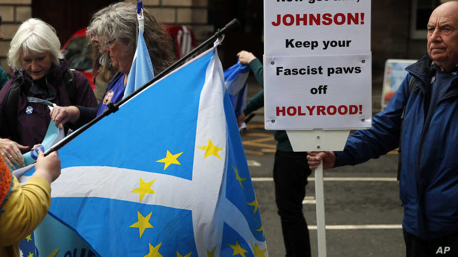 Protesters holding a Scottish flag with European stars gather in front of the Scottish Court of Session in Edinburgh, Scotland,…