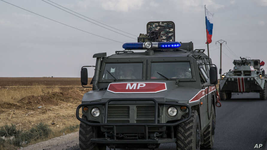 FILE - In this Oct. 24, 2019 file photo, Russian forces patrol near the city of Qamishli, north Syria. Russia's Defense…