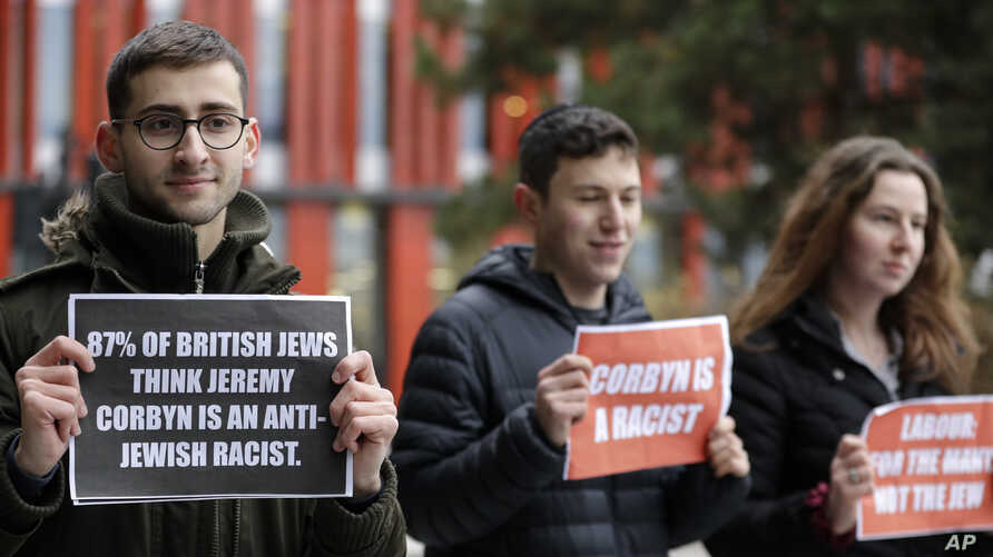 Youngsters hold banners outside the building where Jeremy Corbyn, Leader of Britain's opposition Labour Party attended the…
