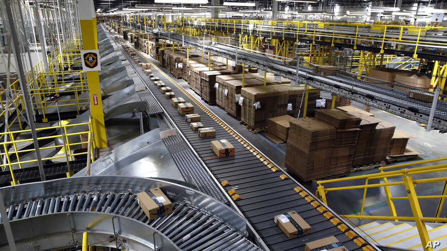 FILE- In this Aug. 3, 2017, file photo, packages ride on a conveyor system at an Amazon fulfillment center in Baltimore. Amazon…