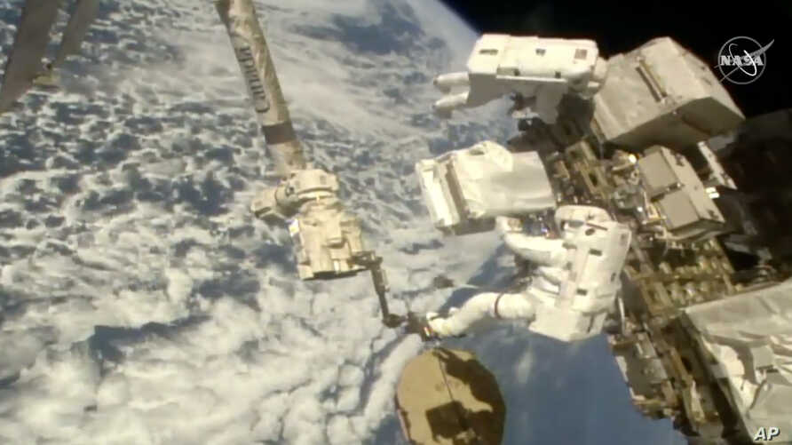 In this image taken from NASA video Italian astronaut Luca Parmitano, lower right, holds a bundle of new pumps for the Alpha…
