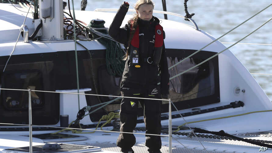 Climate activist Greta Thunberg waves as she arrives in Lisbon aboard the sailboat La Vagabonde, Dec 3, 2019. Thunberg…