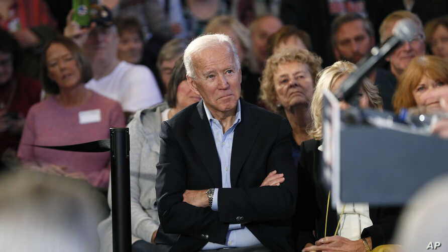 Democratic presidential candidate former Vice President Joe Biden waits to speak to local residents during a bus tour stop.