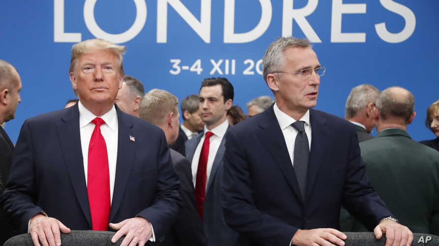U.S. President Donald Trump and NATO Secretary General Jens Stoltenberg wait to take their seats prior to meeting.