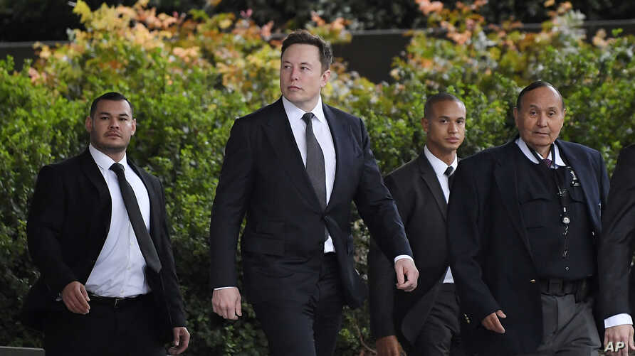 Tesla CEO Elon Musk, second from left, arrives at U.S. District Court Wednesday, Dec. 4, 2019, in Los Angeles. Musk is going on…