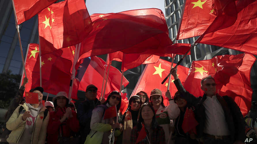 Pro-Beijing supporters wave the Chinese national flags during a rally in Hong Kong, Dec. 7, 2019.