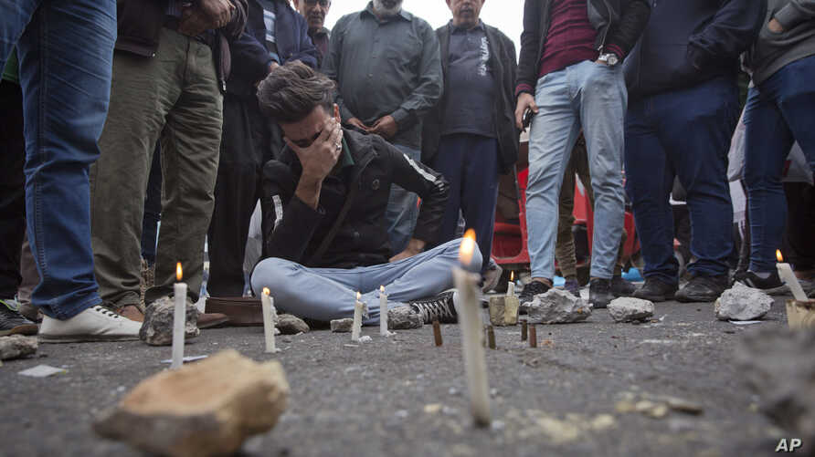 Iraqis gather around a crying man who lit candles by the spot where an Iraqi protester was killed Friday, at Khilani square, in Baghdad, Iraq, Dec. 7, 2019.